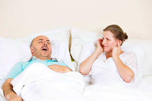 Snoring man, upset woman covering ears, cant sleep.