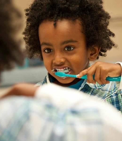 menina escovando dente