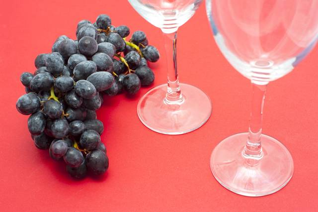 Grapes and Wine Glasses on Red Background