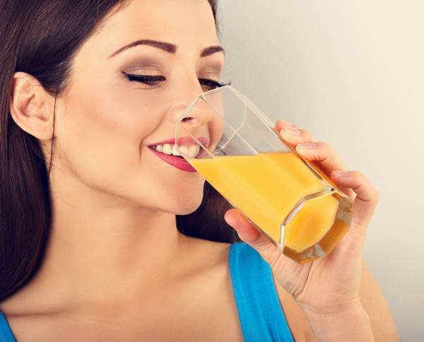Beautiful happy young healthy casual woman drinking orange juice