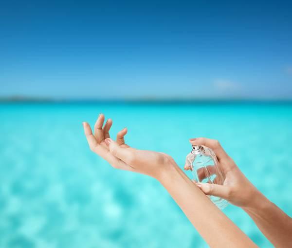 mulher passando perfume praia