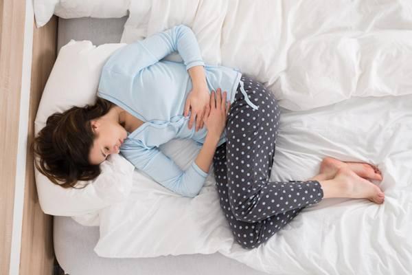 mulher deitada na cama dor doente