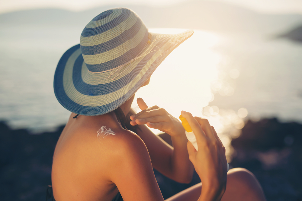 mulher tomando sol protetor solar
