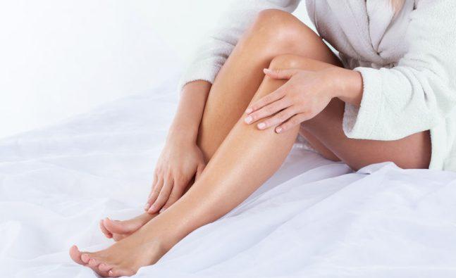 mulher usando oleo creme pernas corpo