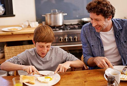 493ss_getty_rf_teen_eating_egg_for_breakfast