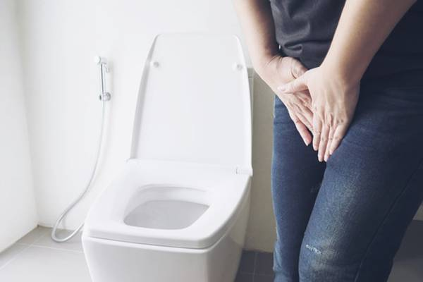 Woman holding hand near toilet bowl - health problem concept