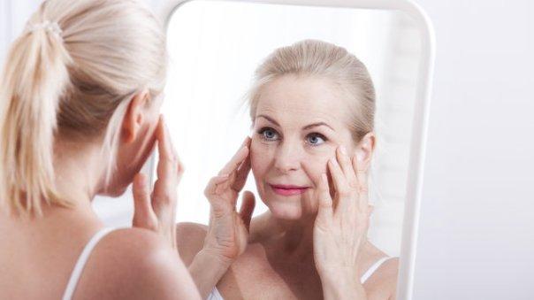 mulher meia idade espelho grisalho rosto
