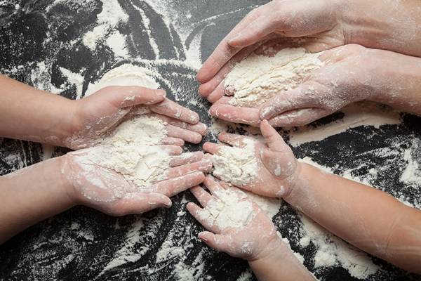 Adults and children's hands hold the flour in the palms of their hands.