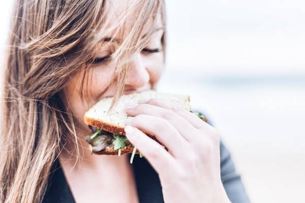 mulher comendo sanduiche unsplash