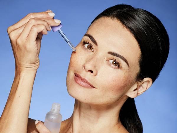 mulher usando serum pele
