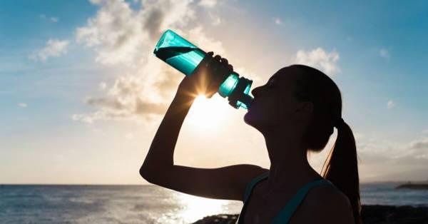 mulher bebendo agua na praia