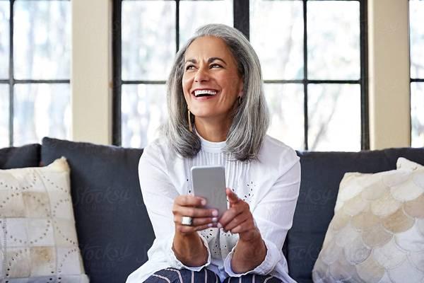 mulher madura usando celular grisalha stocksy united