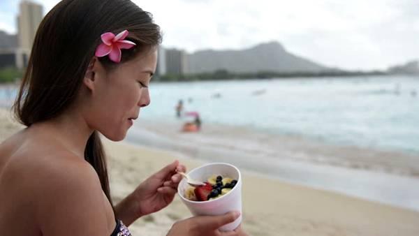 mulher praia comendo shutterstock