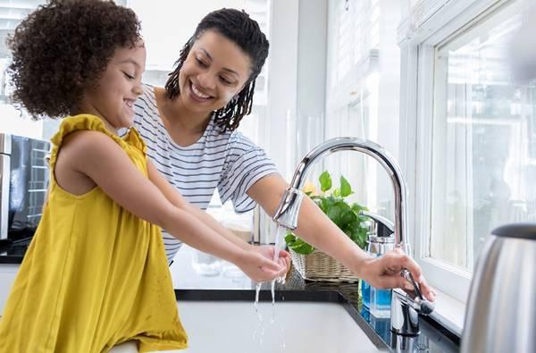 menina e mae lavando a mão