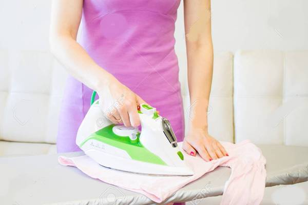 Woman Ironing Clothes Using Iron On Ironing Board