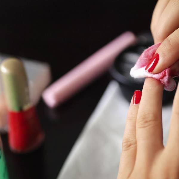 mulher limpando esmalte da unha