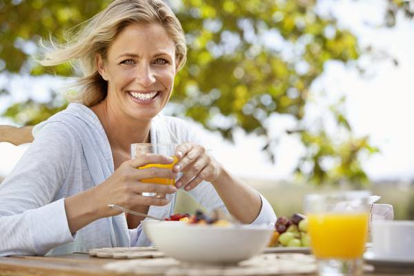 Smiling mature woman with orange juice at breakfast table outdoors
