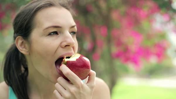mulher comendo maca shutterstock