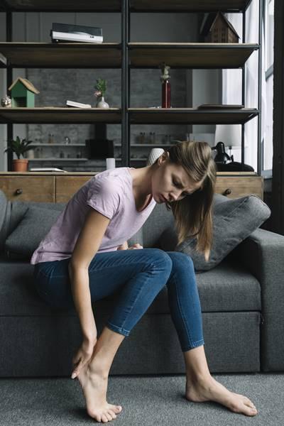 mulher dor pe acidente casa sofá