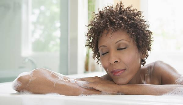African American woman relaxing in bubble bath