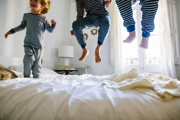 stocksy united criancas pulando na cama