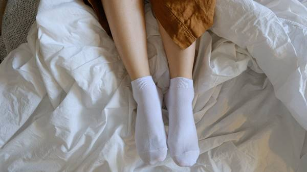 mulher cama meia inverno pernas