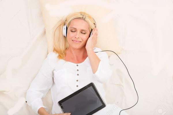 mulher ouvindo musica na cama fone de ouvido