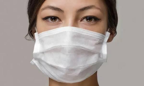 mulher usando mascara descartavel