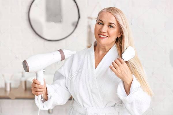 alamy stock photo mulher secando cabelo banheiro
