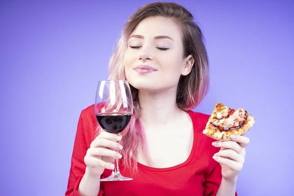 good-looking girl with a slice of pizza and a glass of red wine